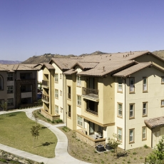 Tan three story apartment buildings with garage and reddish-beige roof and mountains in the background