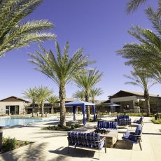 Pool deck area with swimming pool, blue canopies, and a fireplace with blue patio furniture