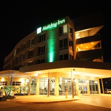 Front facing view of Holiday Inn at night with green accent lighting
