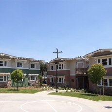 Angled view of apartment homes with a street light and electrical pole to the right and a half basketball court to the left