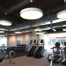 Fitness center with hanging lighting fixtures and ceiling fans