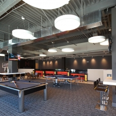 Recreation area with pool table and white hanging lighting fixtures