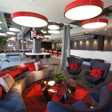 Recreation  area with a grey couch, black loveseats, and red hanging lighting fixtures