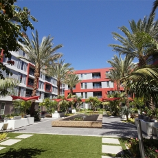Courtyard of apartment building with palm trees and fountain