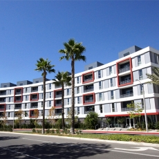 Grey, white, and red apartment building with three palm trees in front