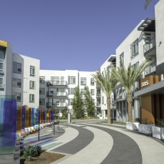 Entrance to leasing center of apartment complex with multi colored panels on the left and two palm trees on the right