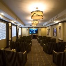 Small movie theatre with two rows of coupled chairs and hung lighting fixtures