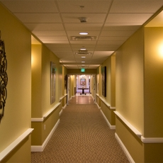 Hallway with lighting fixtures on wall